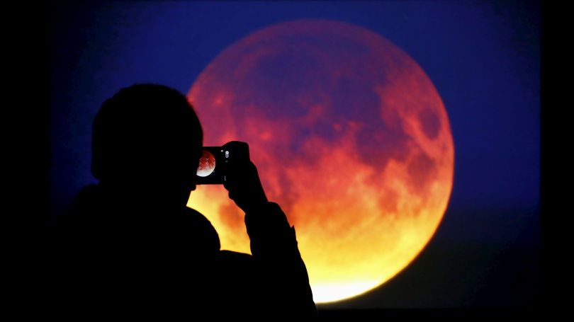 A man takes picture of the screen displaying the moon in Warsaw